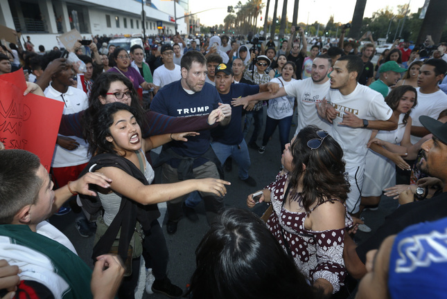 Protestors surround a Trump supporter on S. Almaden Boulevard outside the San Jose Convention Center as Presidential candidate Donald Trump holds a rally in San Jose, Calif., Thursday, June 6, 2016. (Patrick Tehan/Bay Area News Group)