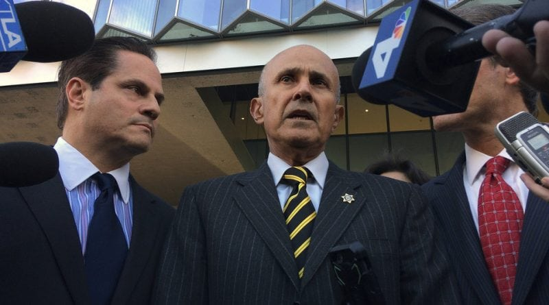 Former Los Angeles County Sheriff Lee Baca, center, talks to members of the media as he walks out of a federal courthouse downtown Los Angeles on Thursday, Dec. 22, 2016. A federal judge declared a mistrial Thursday in the corruption trial of Baca after jurors said they were hopelessly deadlocked. (AP Photo/Brian Melley)