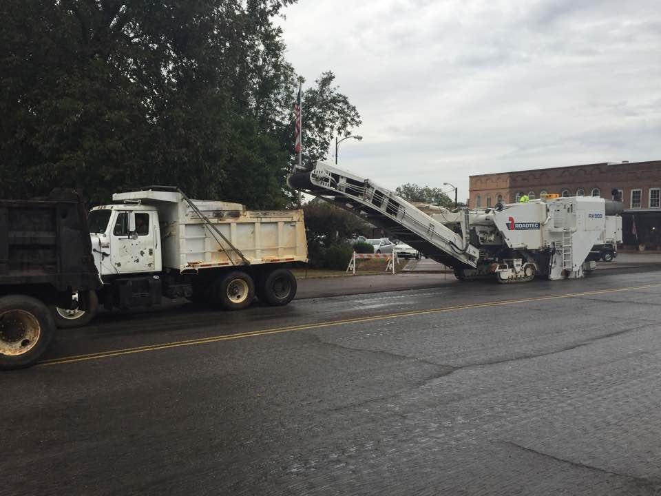 Heavy equipment engaged in repairing and repaving streets and roads in Holly Springs, MS.